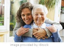 Woman holding elderly woman